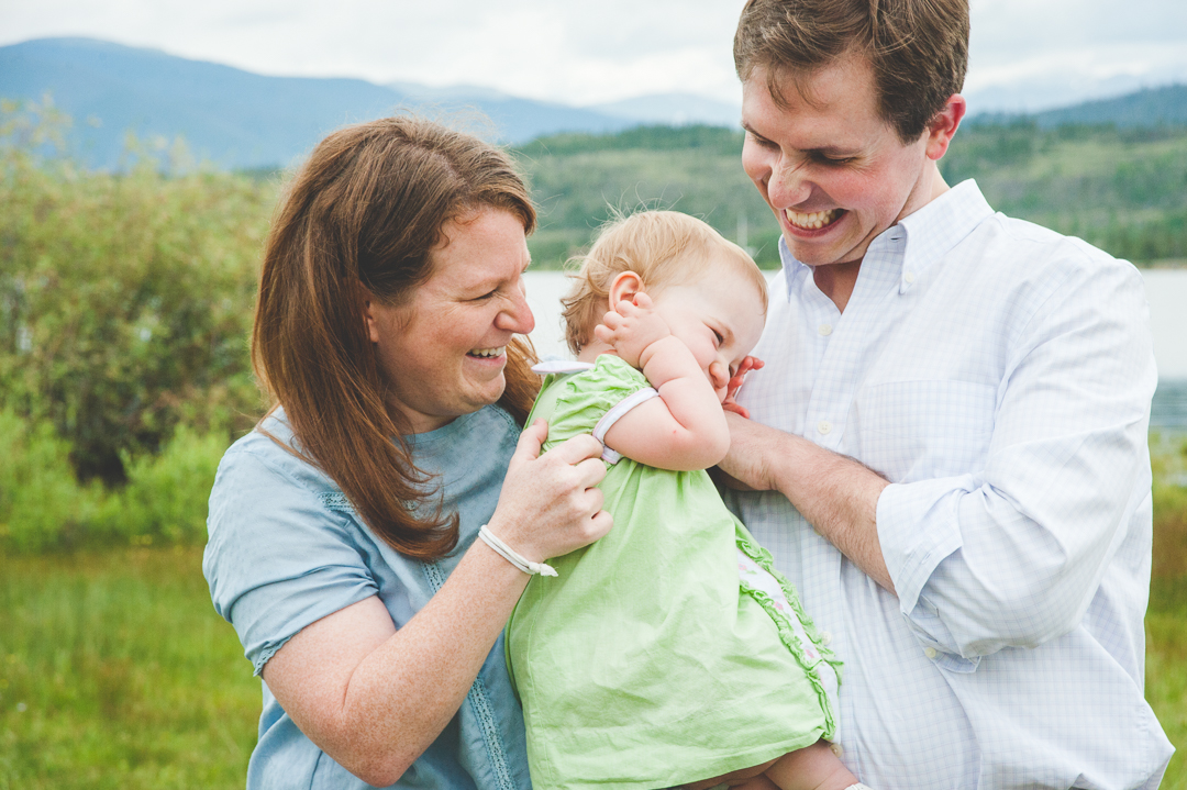 mom and dad elicit a bit of laughter from their sleepy toddler during their family photo shoot near Lake Dillon in Colorado