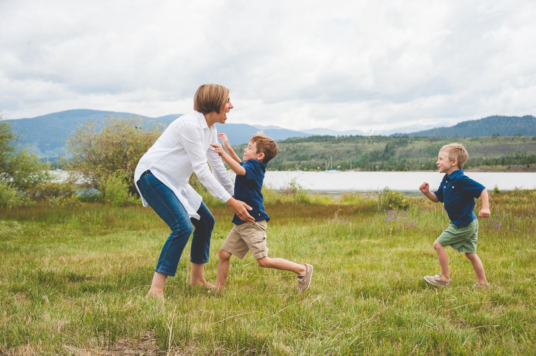 Two young boys run to their mom during their lakeside family photo shoot in Frisco Colorado at Lake Dillon