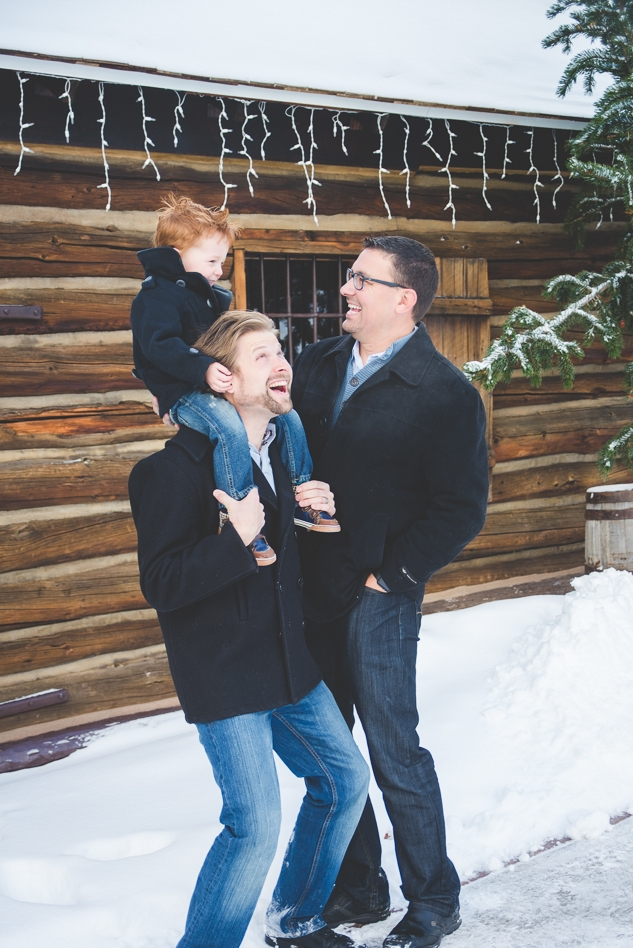 Both dads get their two-year-old son giggling in the snow during their holiday photo shoot in Frisco, Colorado