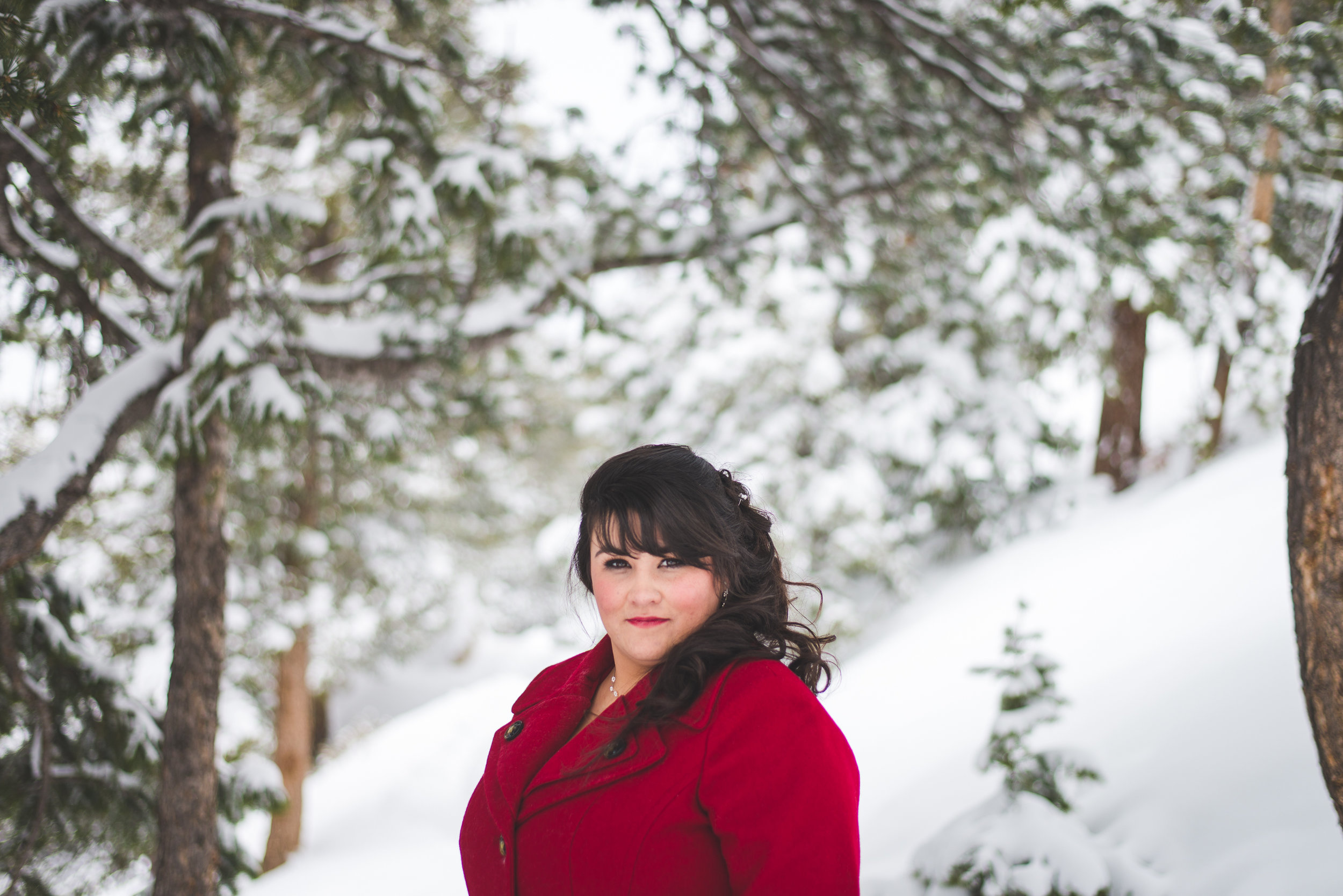 this beautiful Colorado bride chose a bold, red coat to wear over her wedding dress - a great way to add pop and color to the snowy landscape!