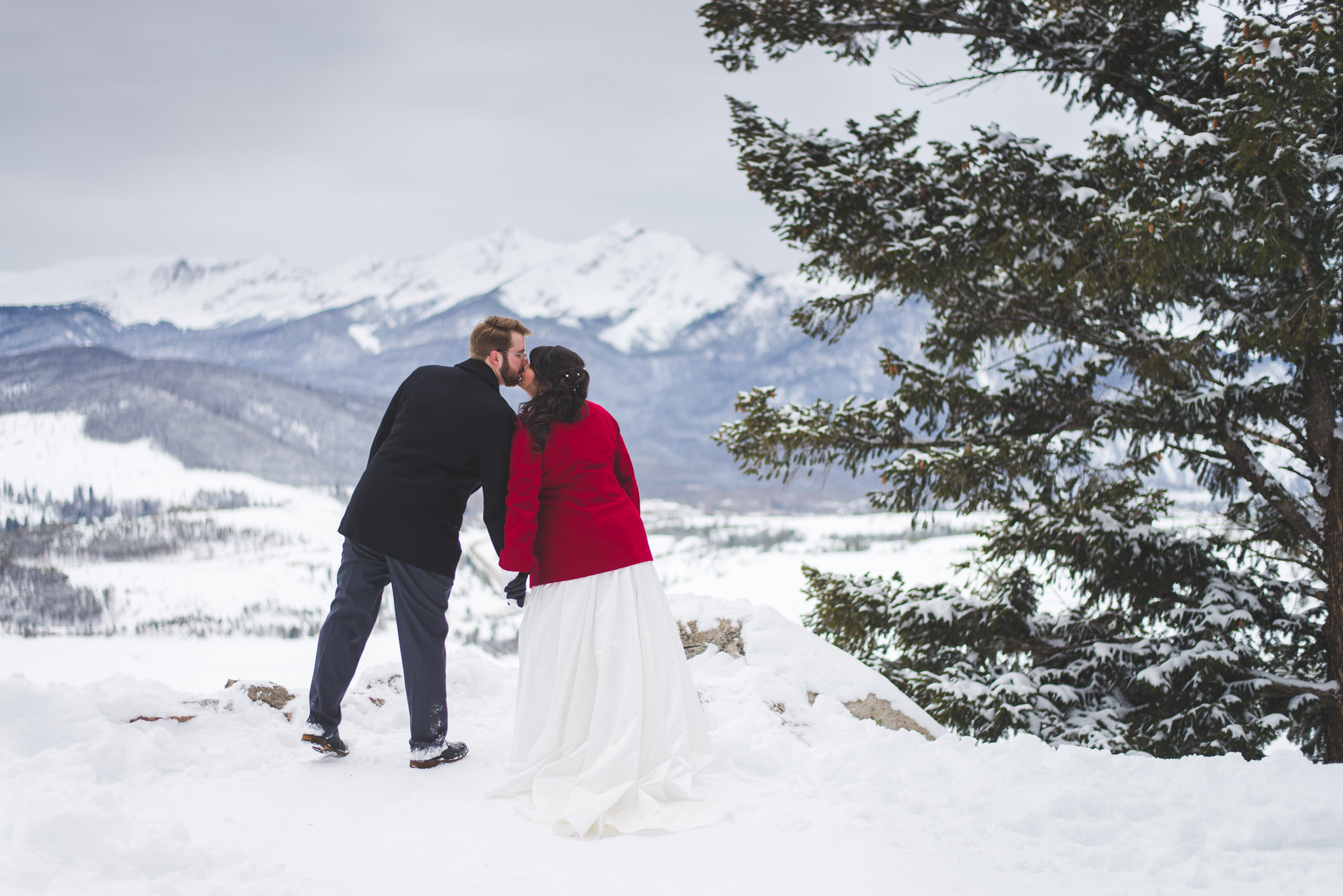 newlyweds kiss at the overlook at Sapphire Point looking out over Lake Dillon and Peak One in Frisco, Colorado