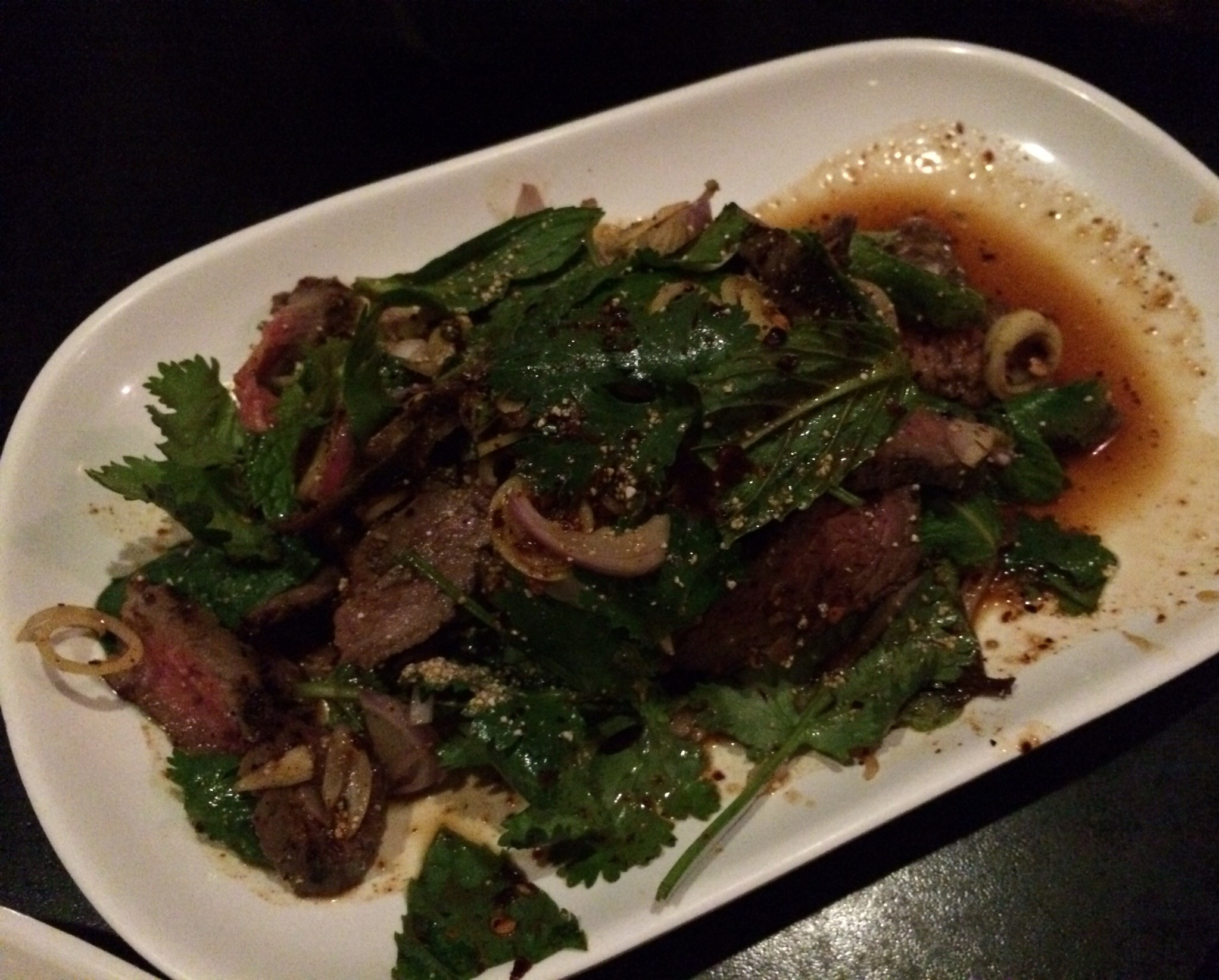 NEUA NAAM TOK - flank steak salad with fish sauce, lime, and chili powder dressing, shallots, lemongrass, mint, cilantro, and toasted rice powder.