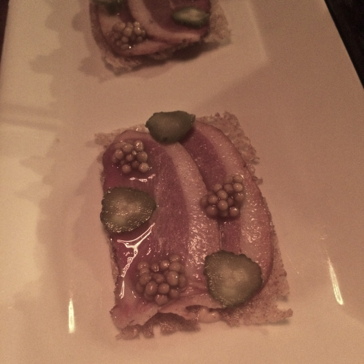 DUCK PASTRAMI WITH PICKED MUSTARD SEEDS, CORNICHONS ON A PUMPERNICKEL CRISP
