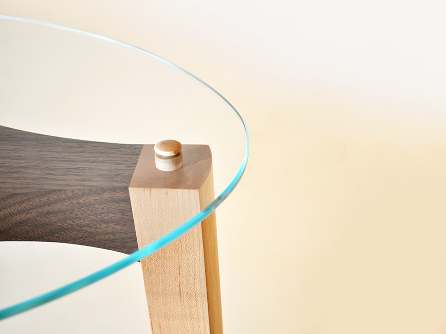 Detail shot of Maurice Vanderlinden's Black Walnut and Maple occasional table, with shaped glass surface.
