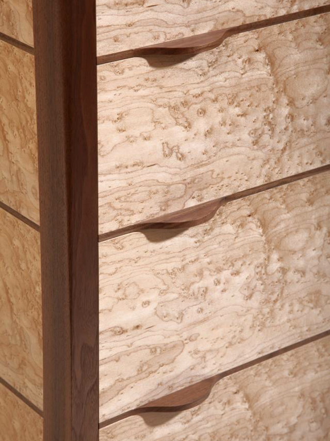 Detail view.Tim Hagon's 'Oculi' Chest of Drawers. The frame is American Walnut with drawers in Artic Maple. The panel and draw fronts are Bird's Eye Maple.