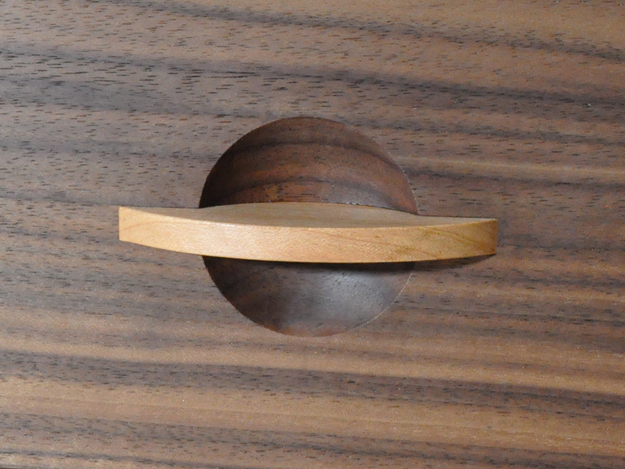 Detail shot of the Cherry handles contrasting with the dark and rich Walnut on Irene Banham's Chest of Drawers.