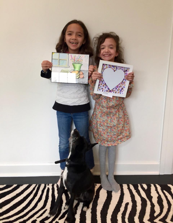 Proud artists Madeline and Agatha Holloway, McGilvra Elementary School classmates, pose with Agatha's dog Tuxedo.