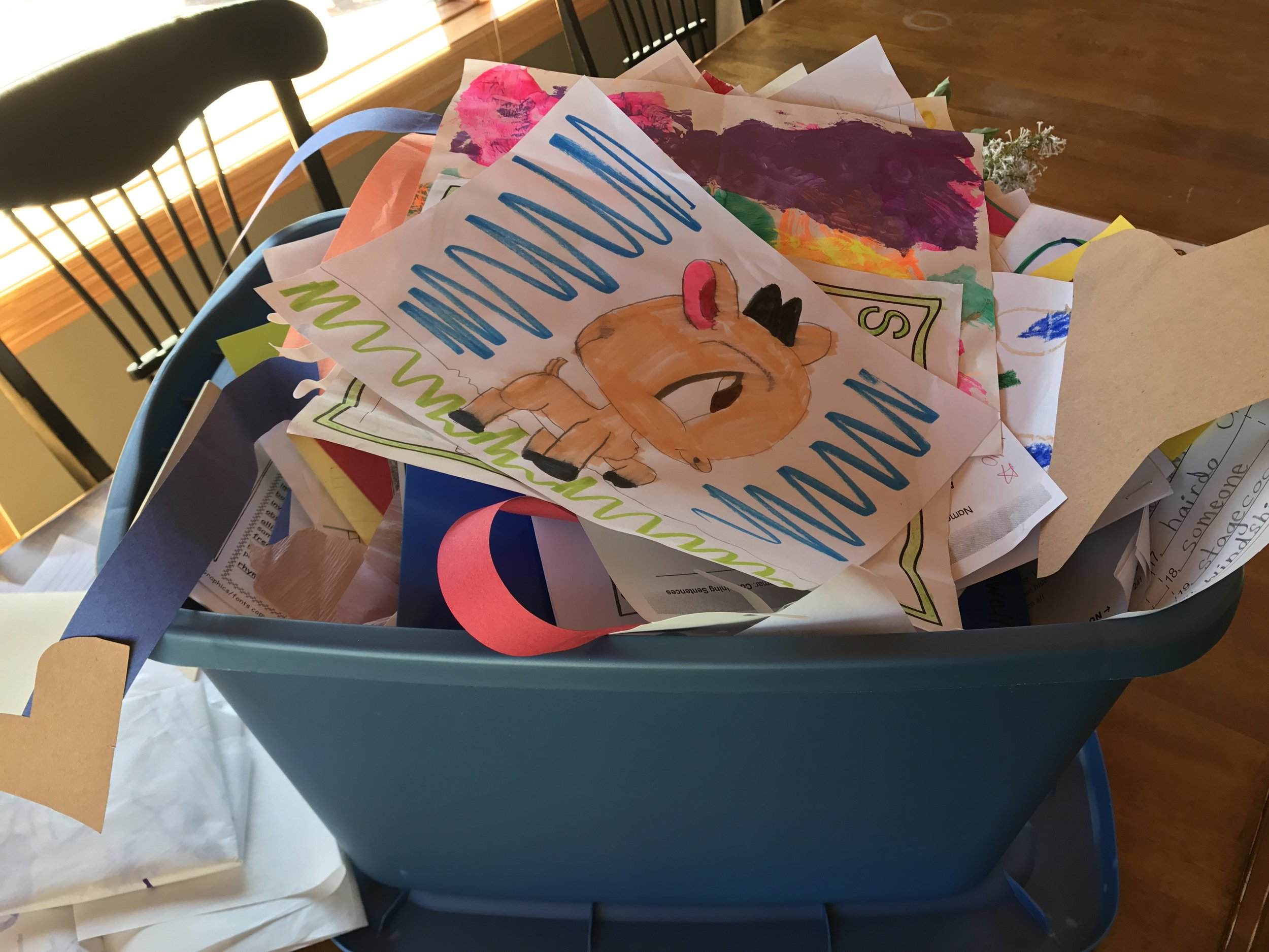 Collect school projects, artwork, and drawings in a bin throughout the year.