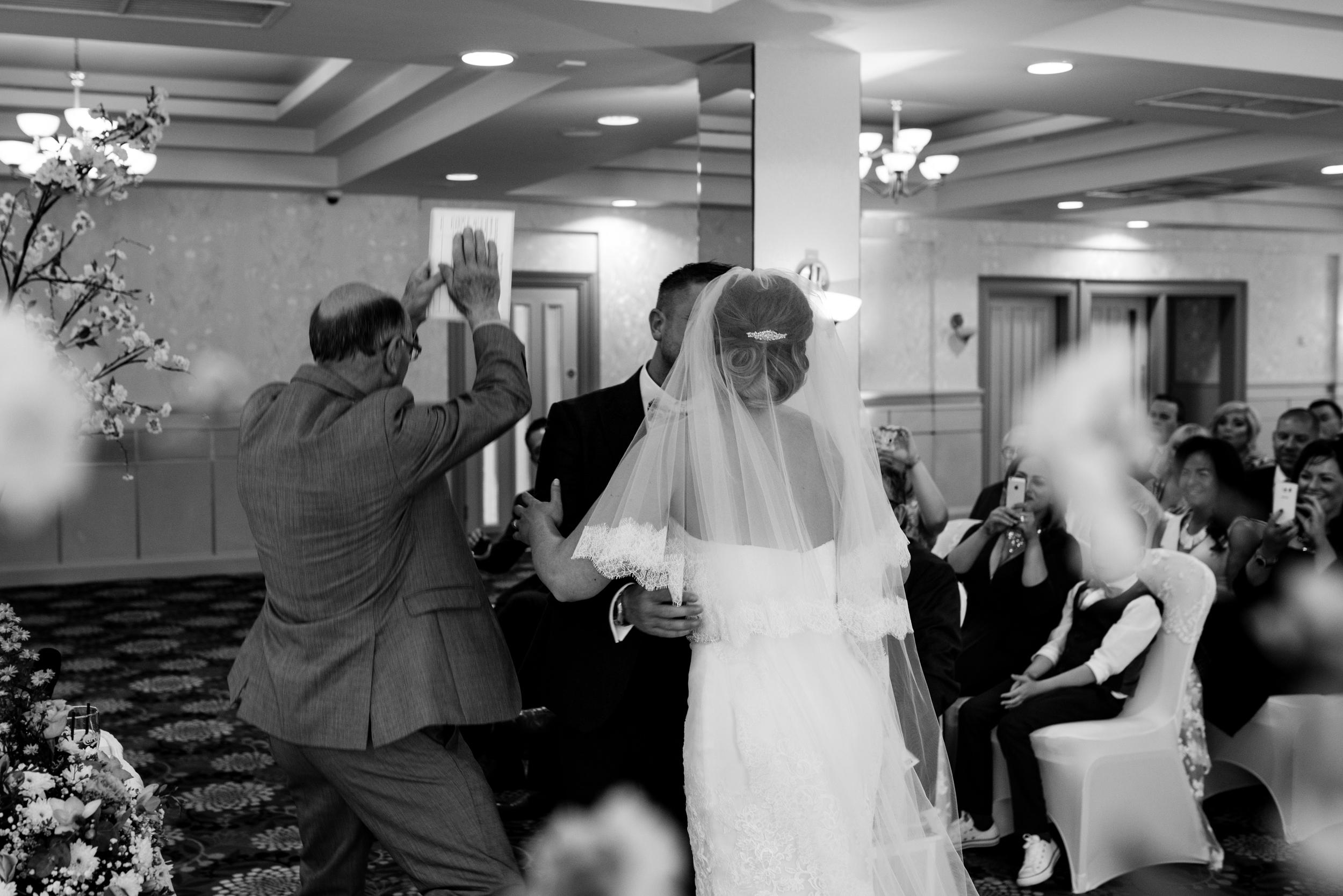 Belfast Wedding Photographer purephotoni Ramada Plaza ceremony bride and groom kiss