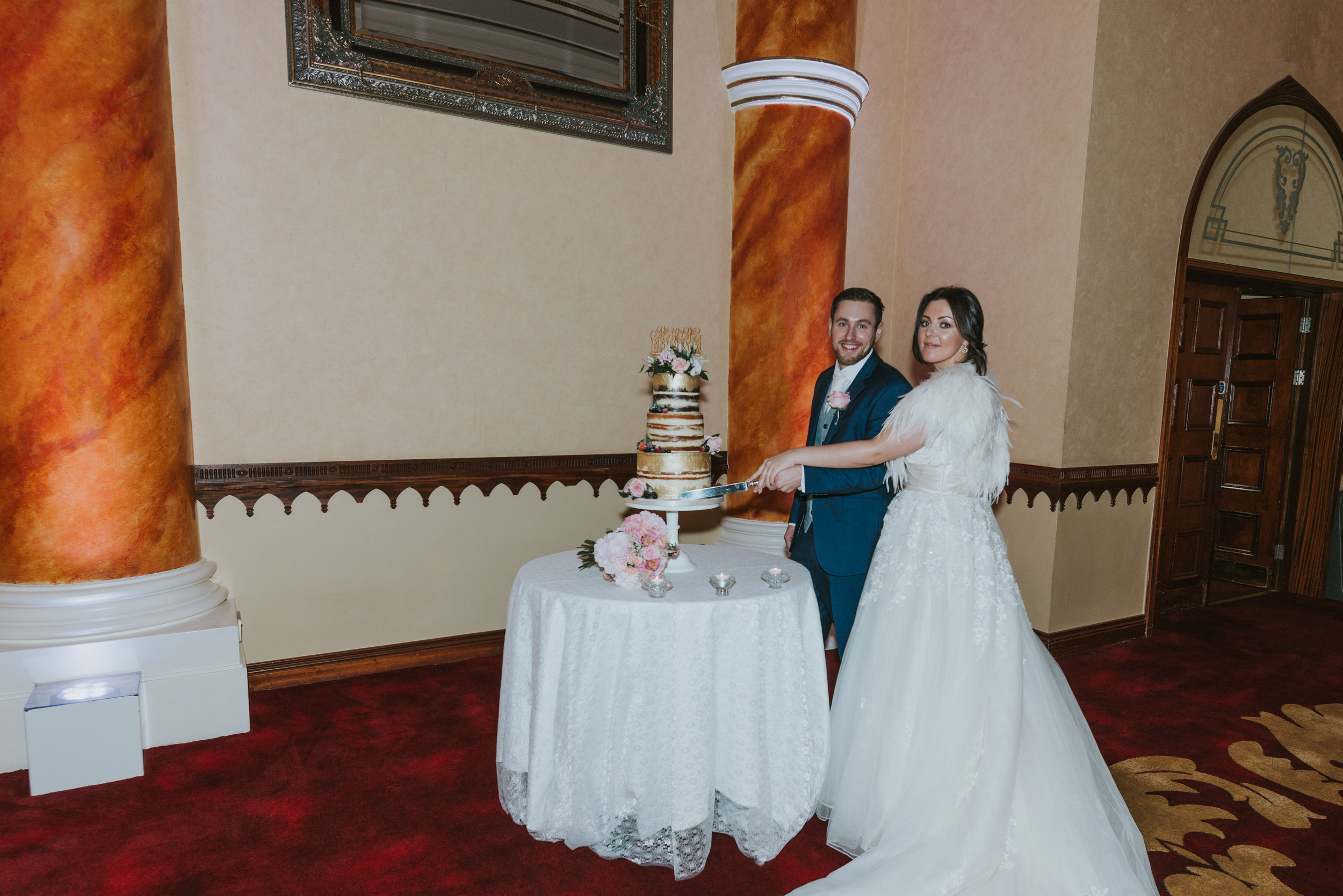 Tullyglass House Hotel wedding groom bride cutting the cake