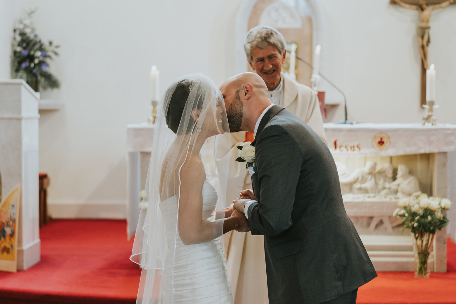 Tullyglass Hotel wedding bride and groom kiss ceremony