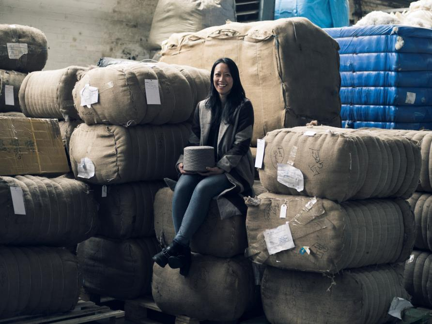 Sitting on bales of fibre, a spool of Khangai yak yarn and wearing the Tengri Chevron coat made of yak fabric.