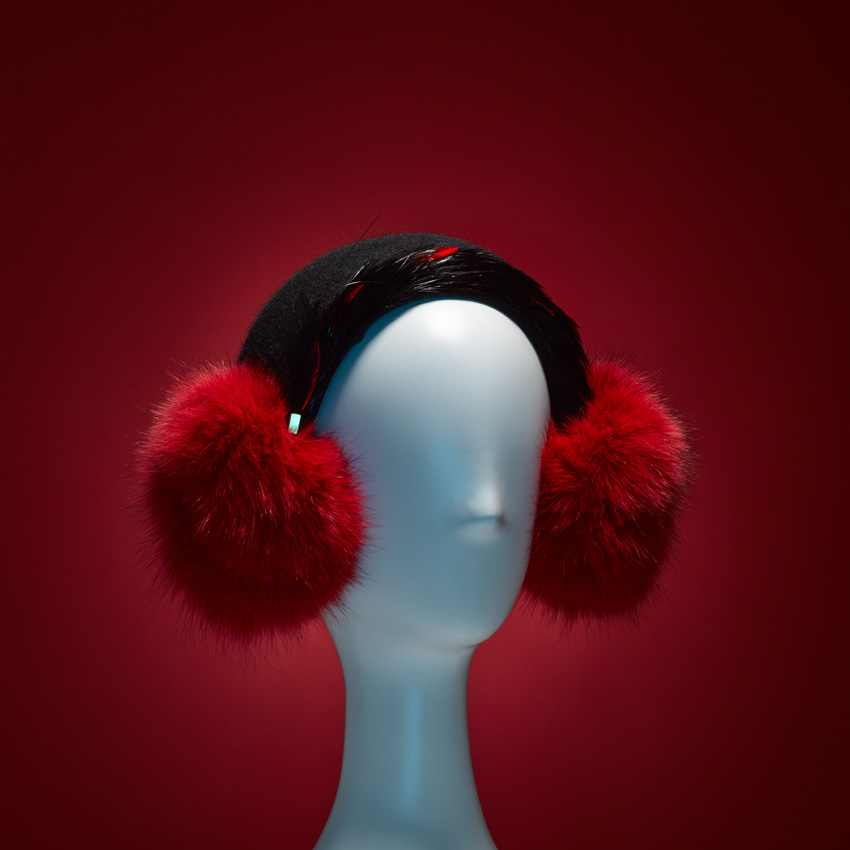 EL   Our EL Sculpted wool earmuff with FAUX fur poms, red and black coque feather band and brass embellishment. Hand-sewn 100% cotton Japanese grosgrain sweatband. Lined with black shearling.   SHOP THE LOOK HERE!