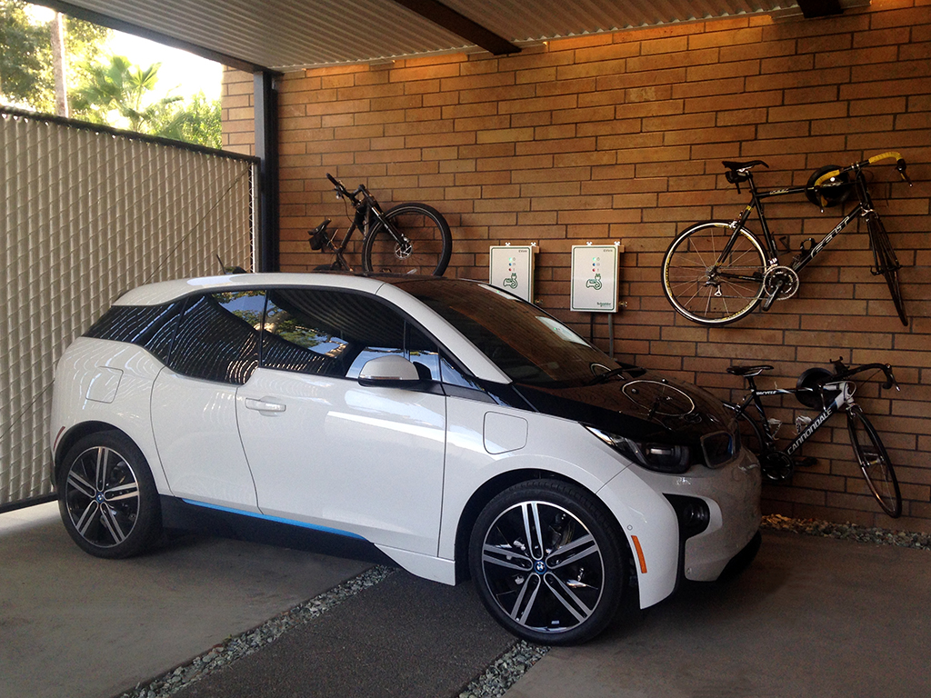 Quick charge dual electric car charging stations and bicycle storage at carport that doubles as covered entertaining space with LED wall grazers, white metal panel ceiling and Texas limestone walls..