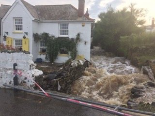 Floodwater rushes down the river running through the centre of Coverack