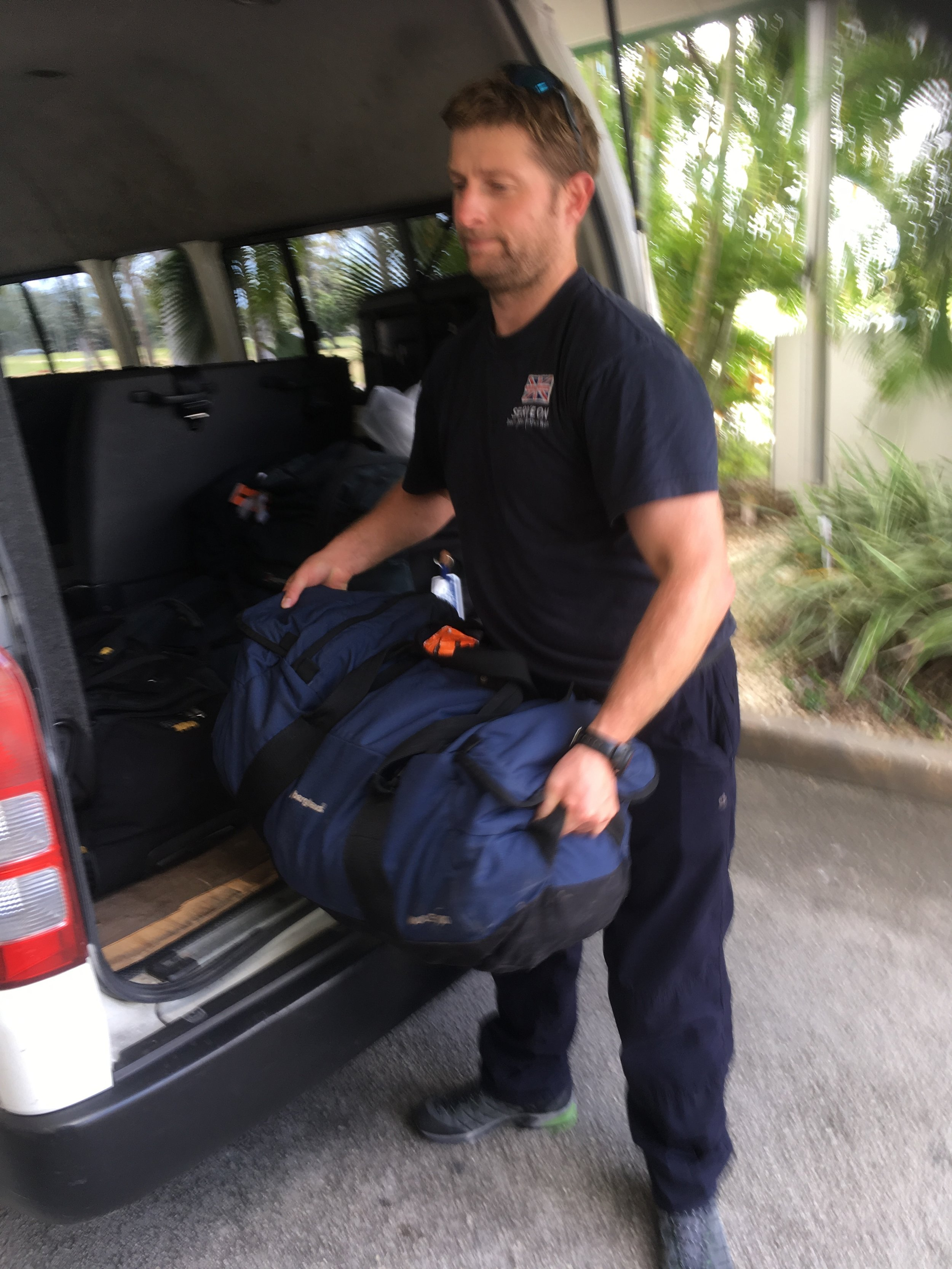 Tom helps the team move their gear to the waiting aircraft