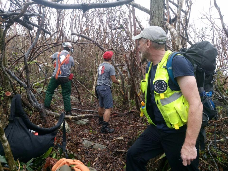 Simon leads efforts to cut a route to the site he identified for a repeater station.