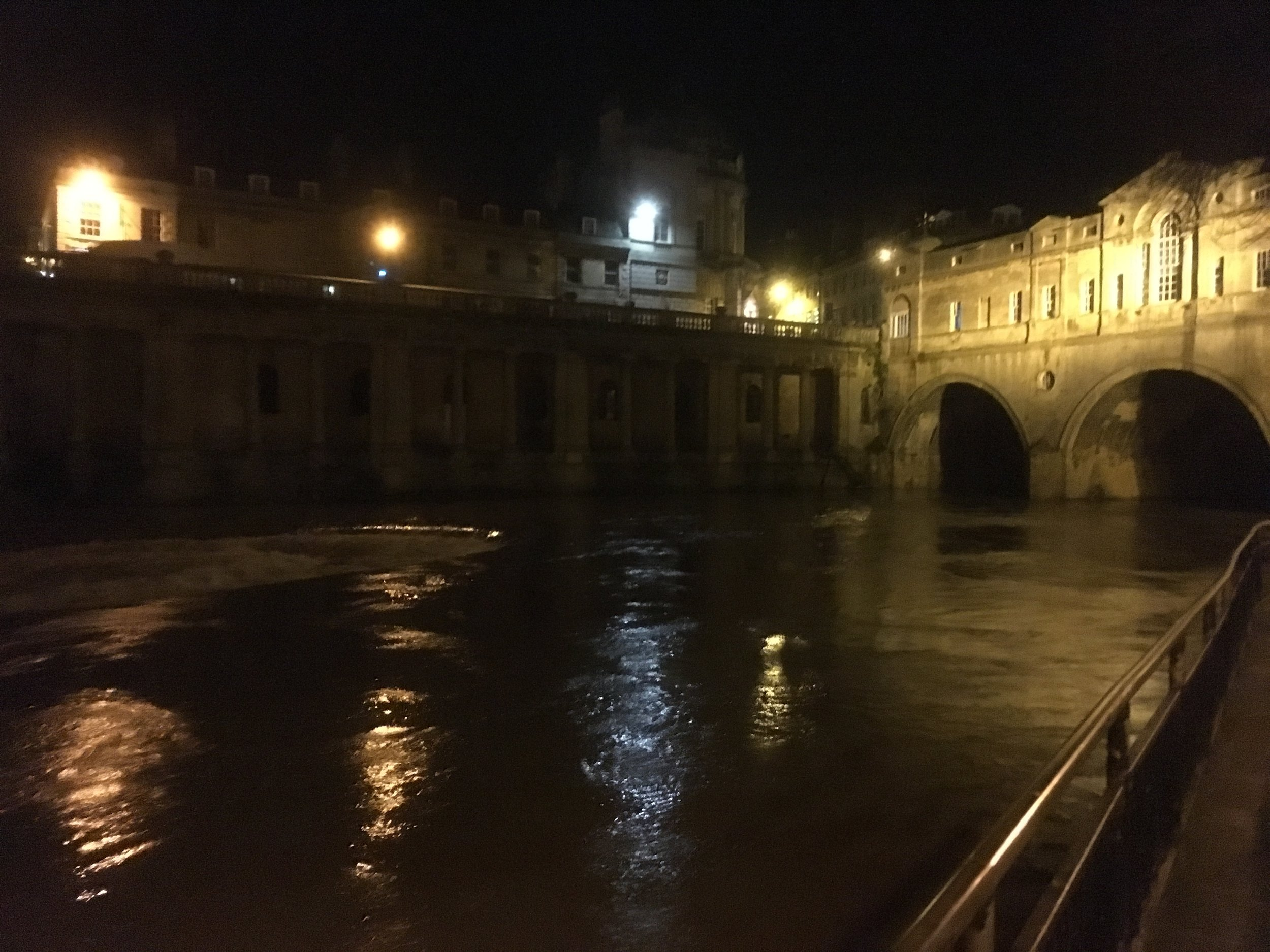 Millions of gallons of flood water pouring over the weir below Bath's famous Pulteney Bridge.