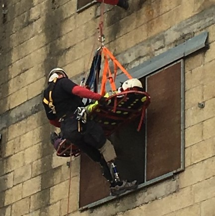 Serve On ambassador and UK Invictus Games team member Pete Dunning stretchering a 'casualty' from a building during final assessment to become an operational member of Serve On International Response Team.