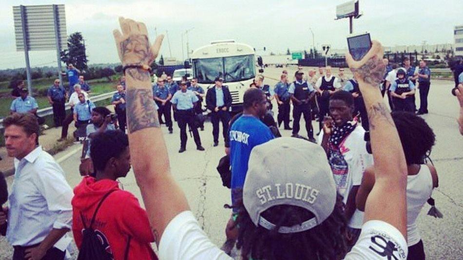 A protester raises both hands during the I-70 shutdown demonstration on Sept. 10.  IMAGE:@MEDIABLACKOUTUSA ON INSTAGRAM