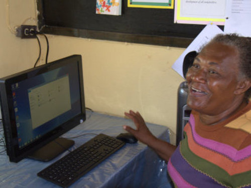 School Principal, Ms Jones, is delighted to receive the new computer equipment.