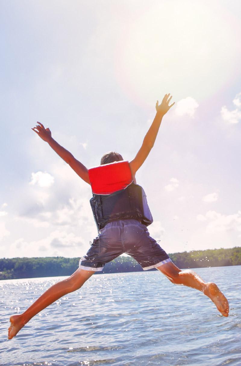 Boy jumping off boat