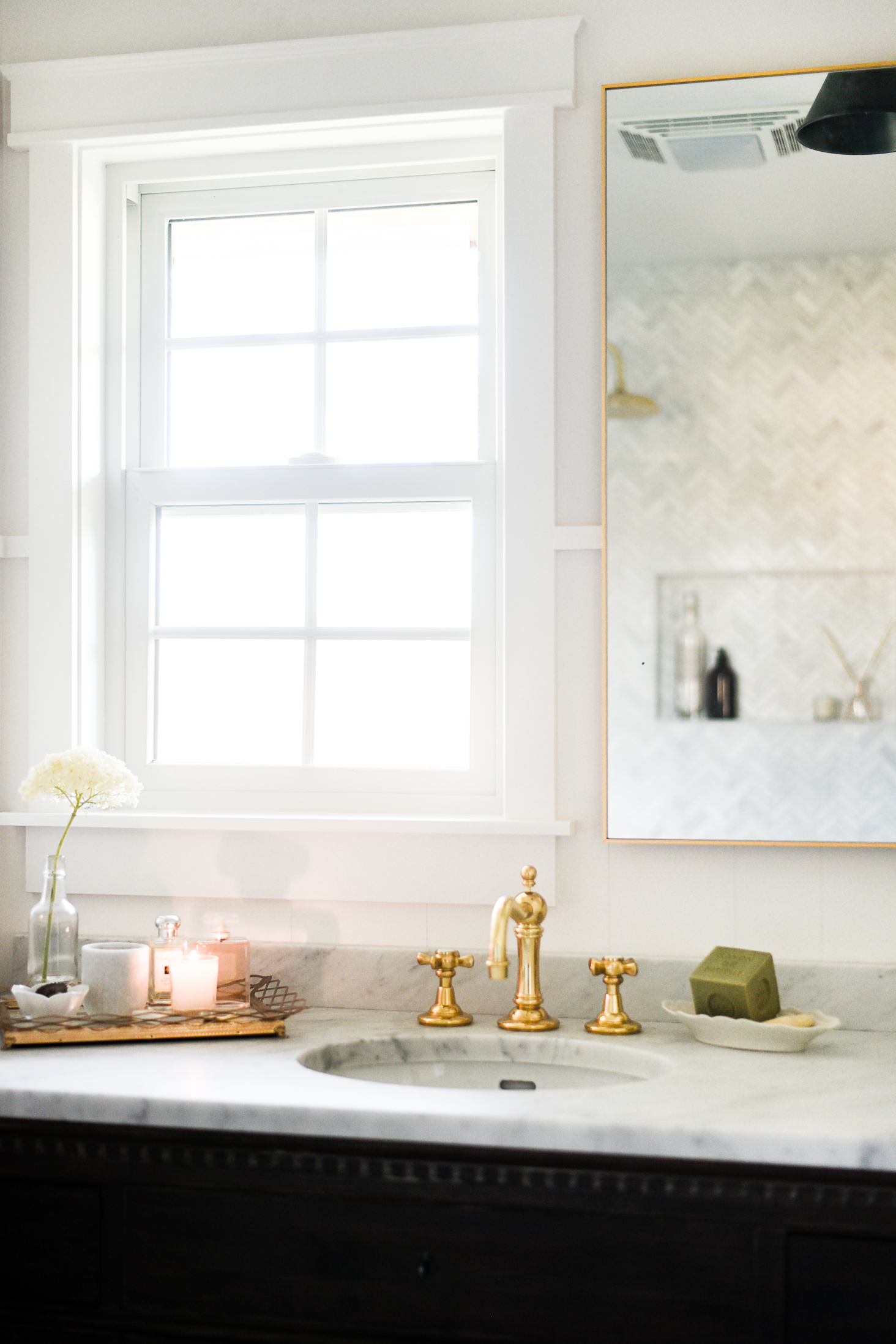 Take a peek into this beautiful guest bathroom remodel full of marble, brass, and pretty details!