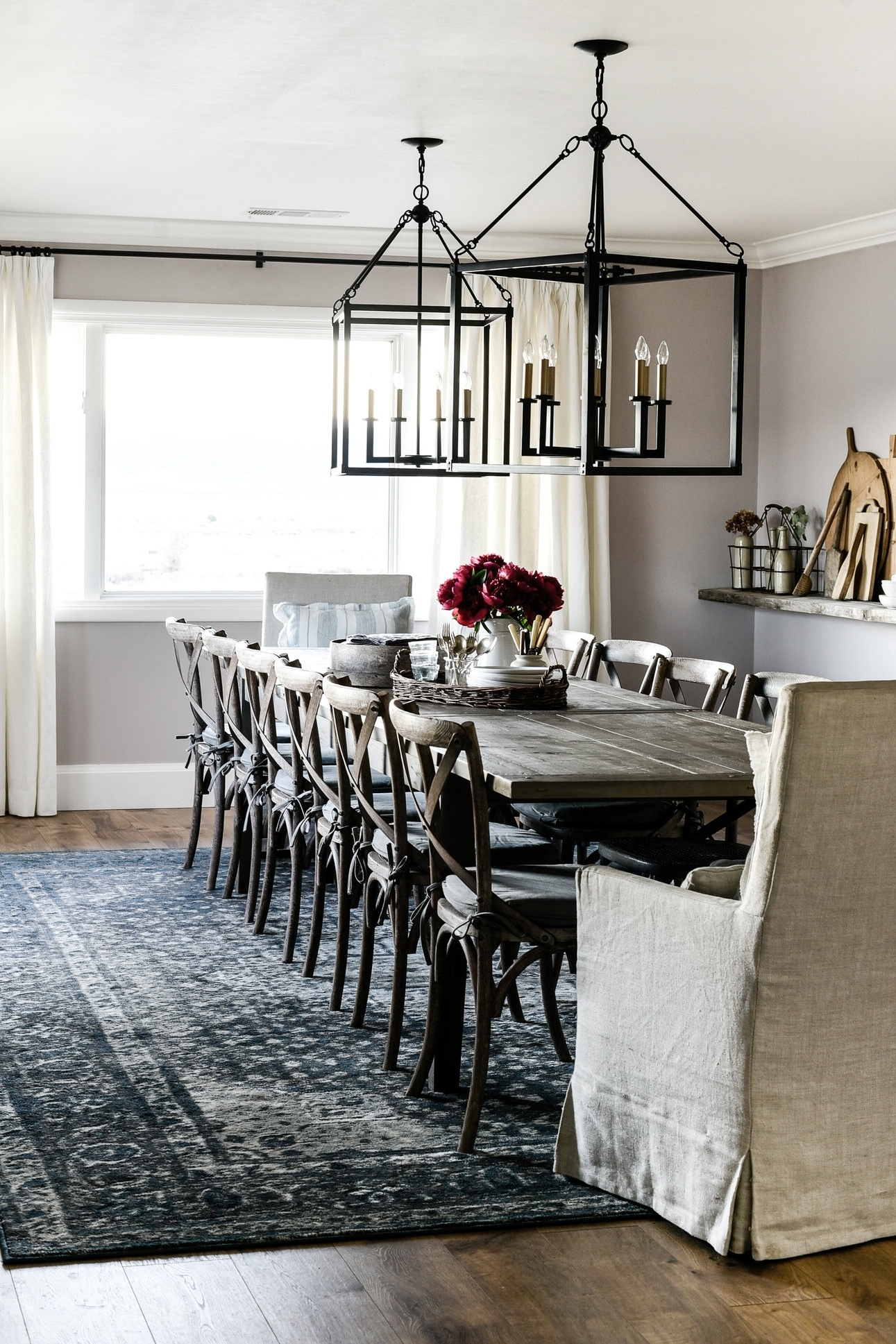 Dining Room - The dining room boasts pink walls with pops of blue and lots of vintage farmhouse decor. The oversized lights add just the right amount of drama!