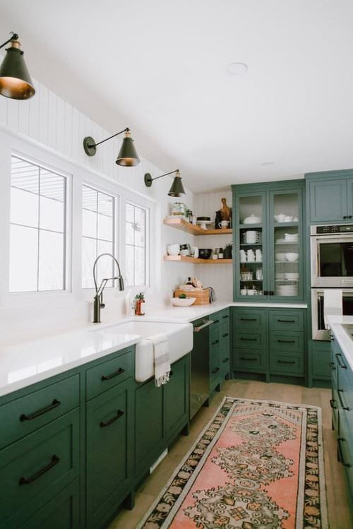 Green cabinets with open shelves and vintage rug in kitchen by Jaclyn Peters Design