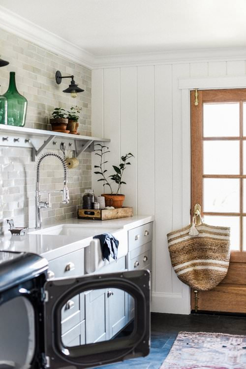 A beautiful laundry room design with gray cabinets and white shiplap from boxwoodavenue.com