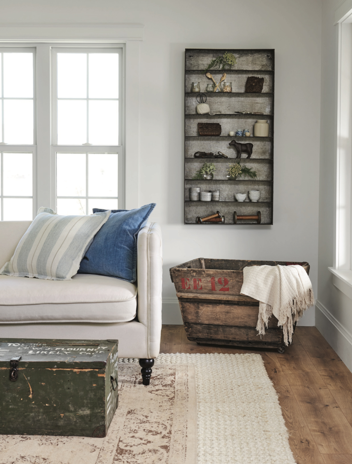 Farmhouse+living+room+with+metal+spice+shelf+wall+art+and+vintage+army+trunk+coffee+table+with+tufted+couches+and+vintage+champagne+crate+|+#farmhousestyle+#farmhouse copy.jpg