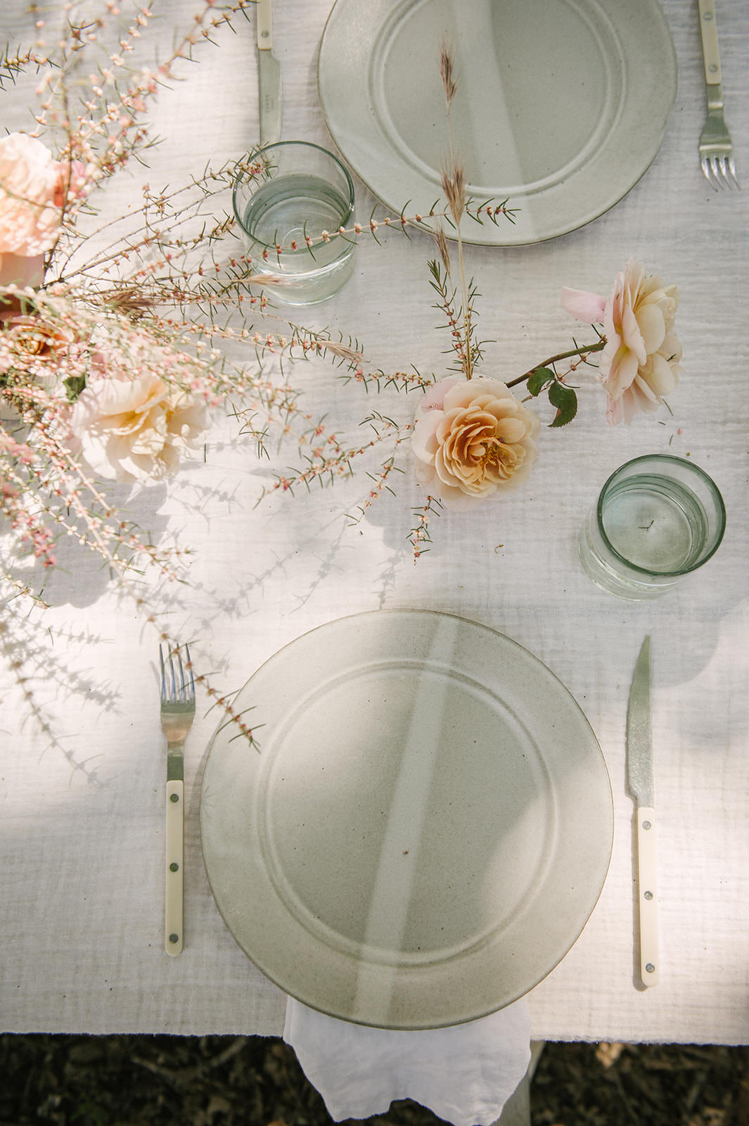 White layered tablescape with roses and linen for #entertaining #tablescape ideas by Jenni Kayne.