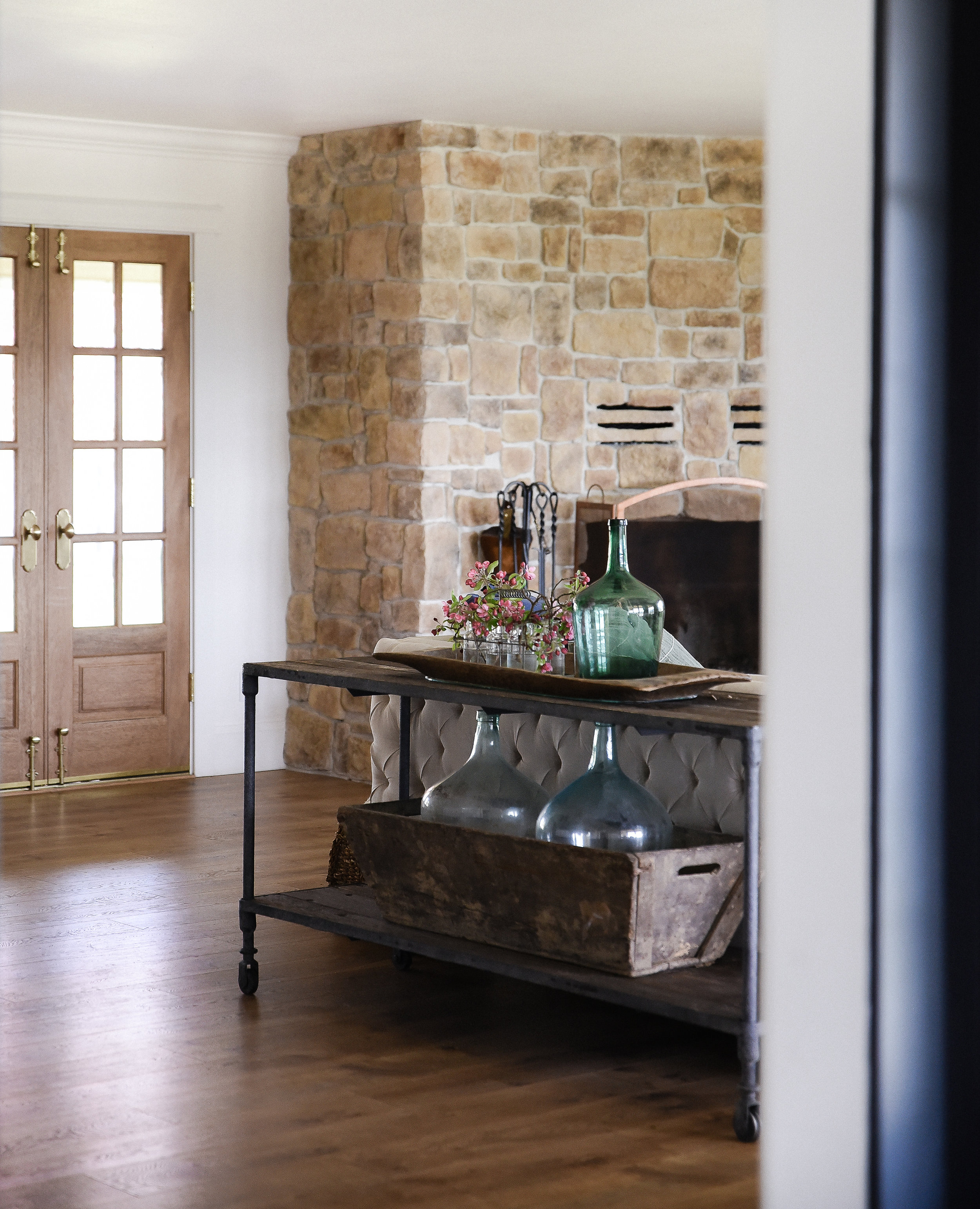 Vintage inspired European modern farmhouse with wood french doors and stone fireplace. #summerdecoratign #springdecor #farmhousestyle #boxwoodavenue