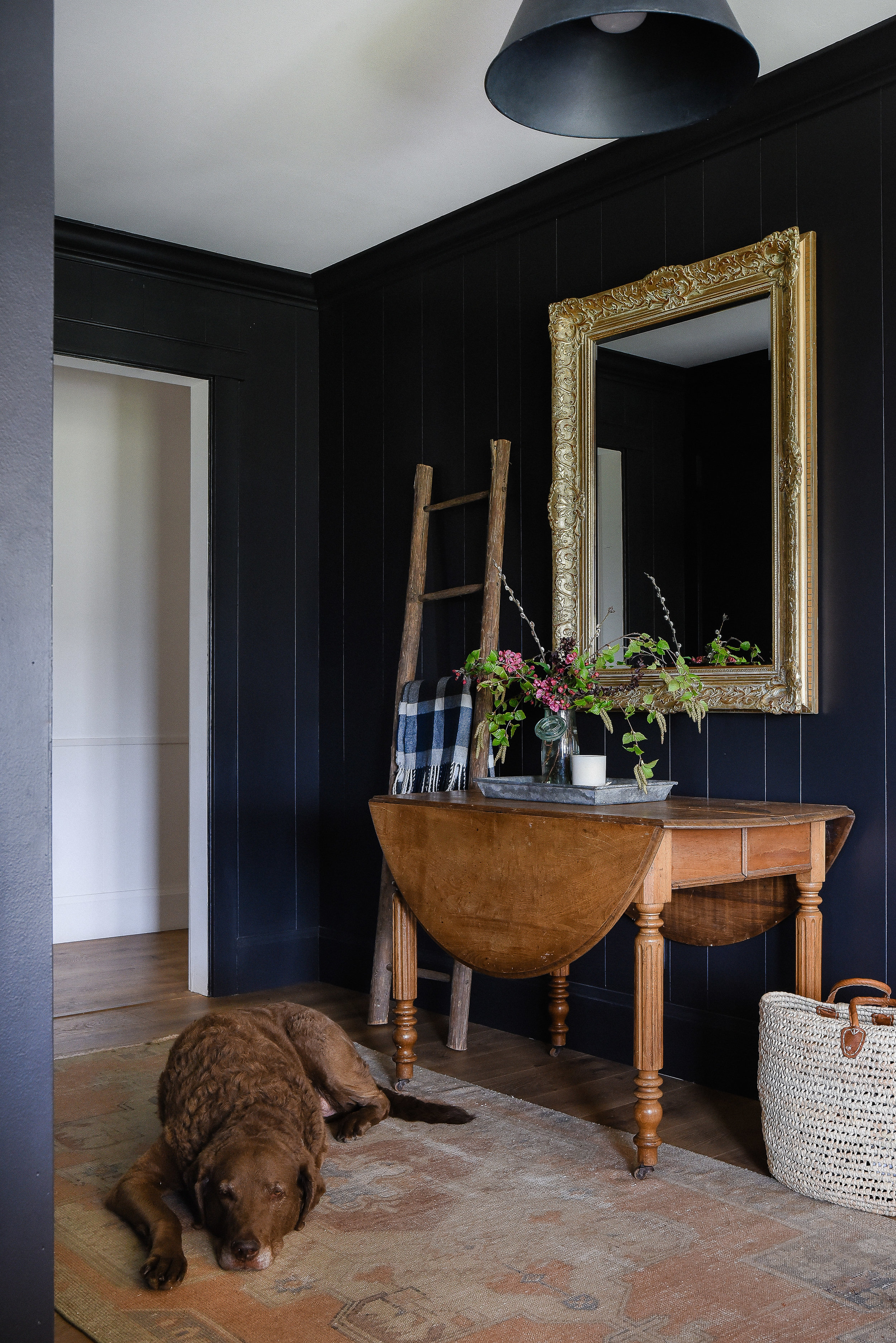 Dark paneled mudroom entry with vintage table and antique gilded mirror and vintage area rug with dog and market basket #farmhousestyle #antiquedecor #blackpaint