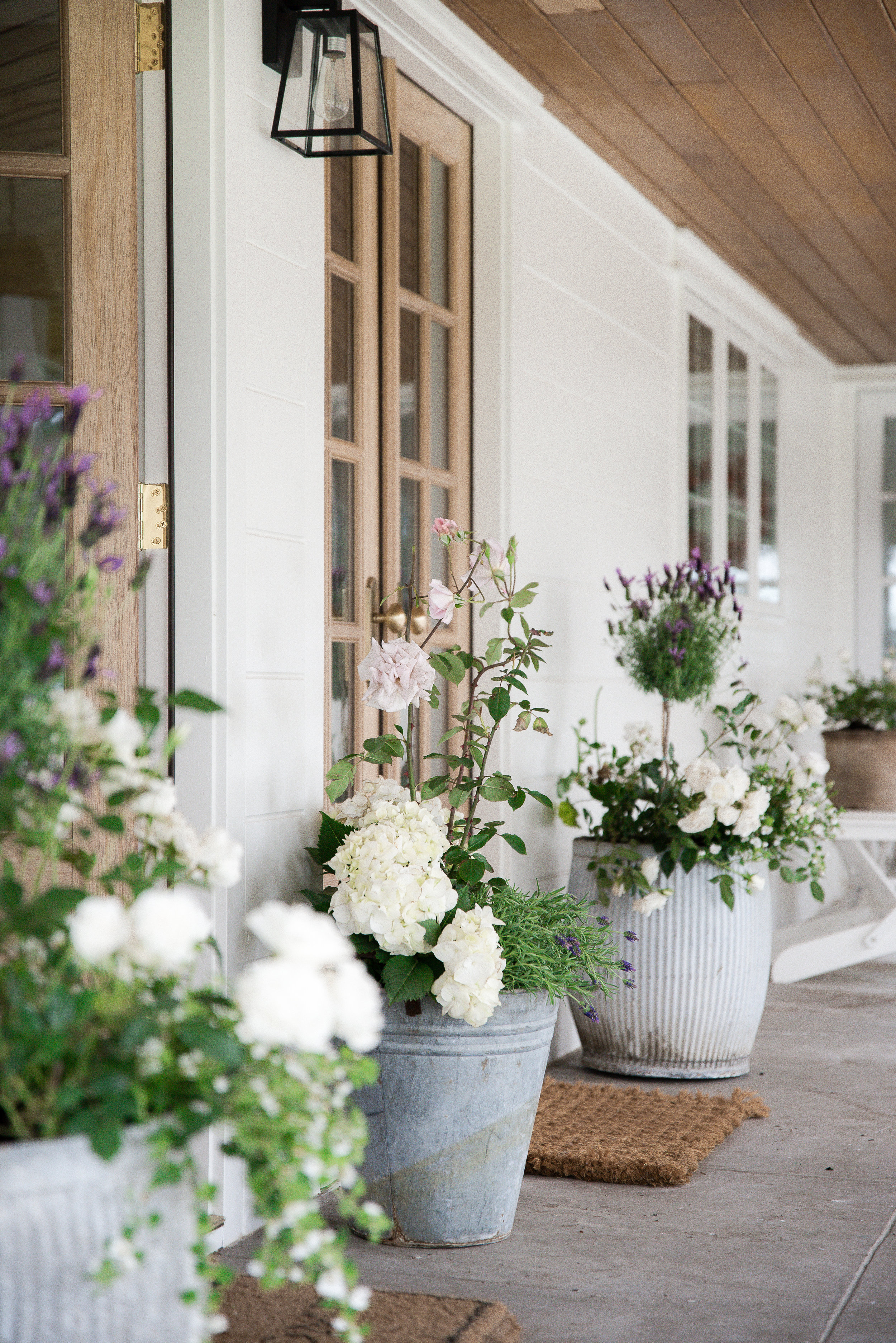 Beautiful summer flower pot and farmhouse porch design by Boxwood Avenue  - Lavender topiary, hydrangea, and roses in vintage galvanized pots. #flowerpots #summergardening