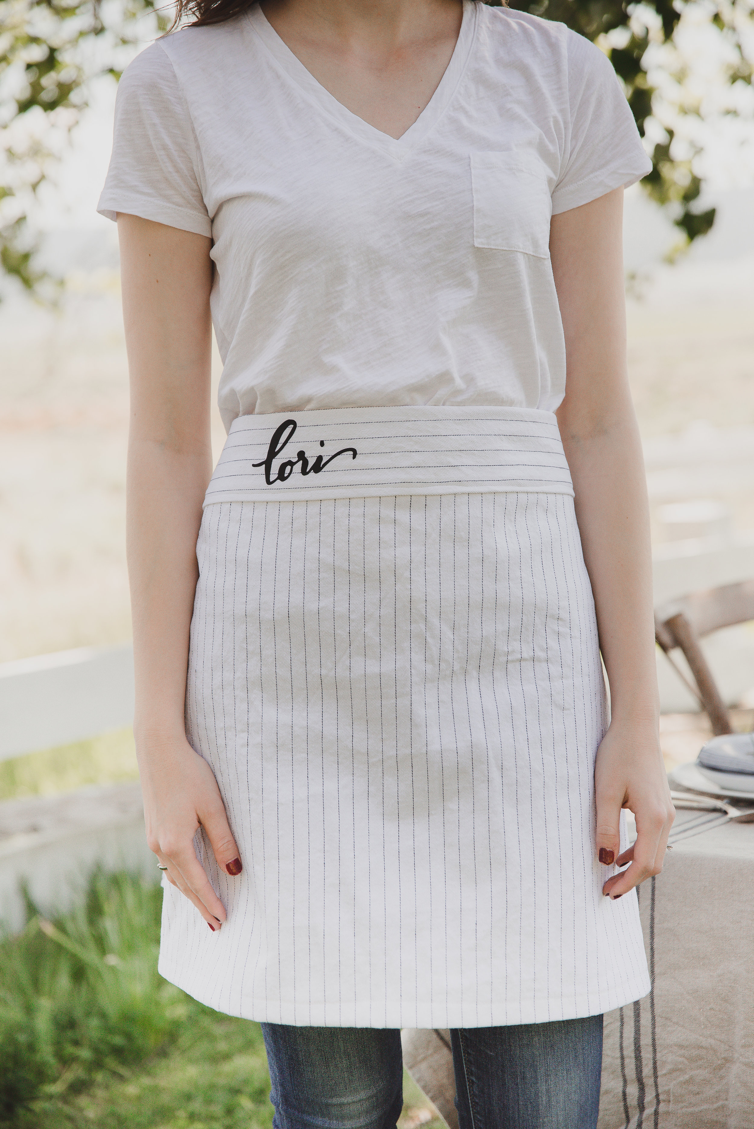 Make this easy half apron with this free apron pattern guide (with video!) - this is a great start into sewing for beginners! Striped farmhouse half apron with monogram. #sewingpatterns #freepatterns #halfapron #sewingproject