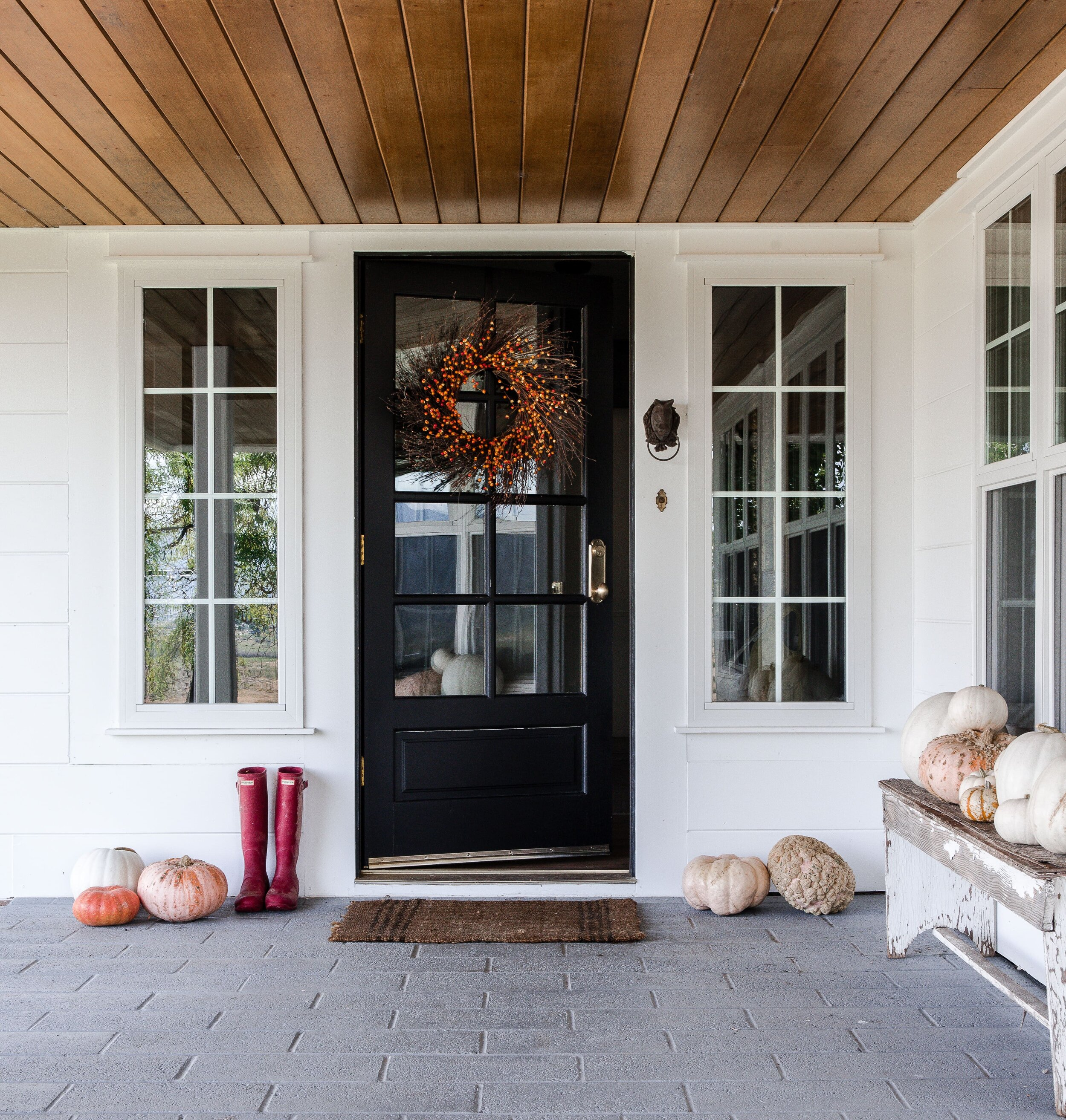 Fall farmhouse front porch with black door, fall wreath, and pumpkins. #fallporch #falldecor #falldecorating