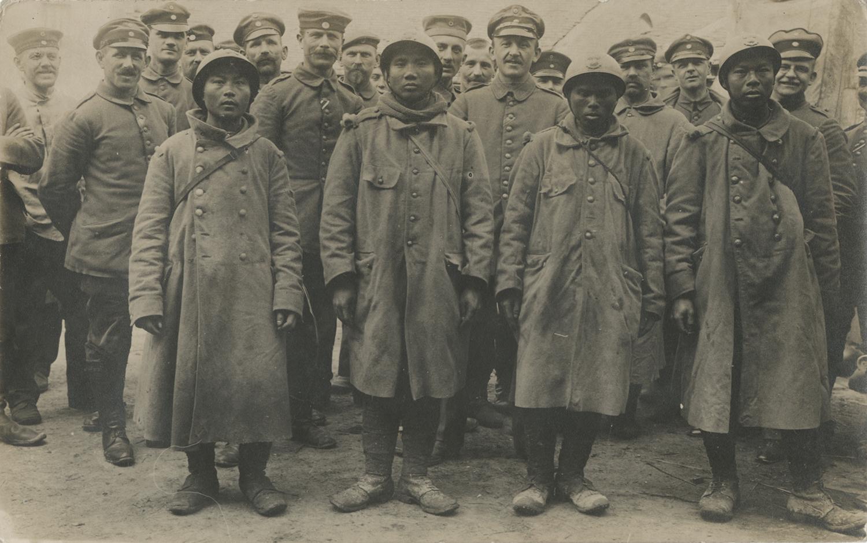 Postcard depicting four Asian men in uniform. ca 1914 - 1918