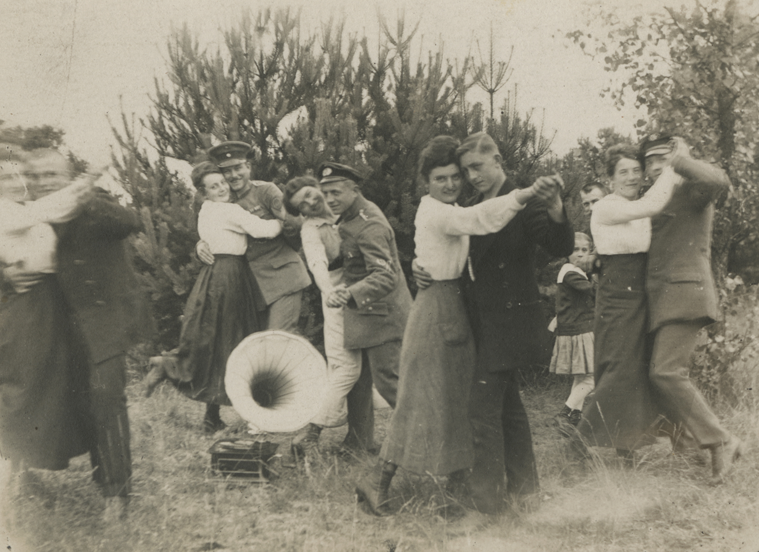 Men, women, and a child dancing outdoors by a gramophone. ca. 1914-1918