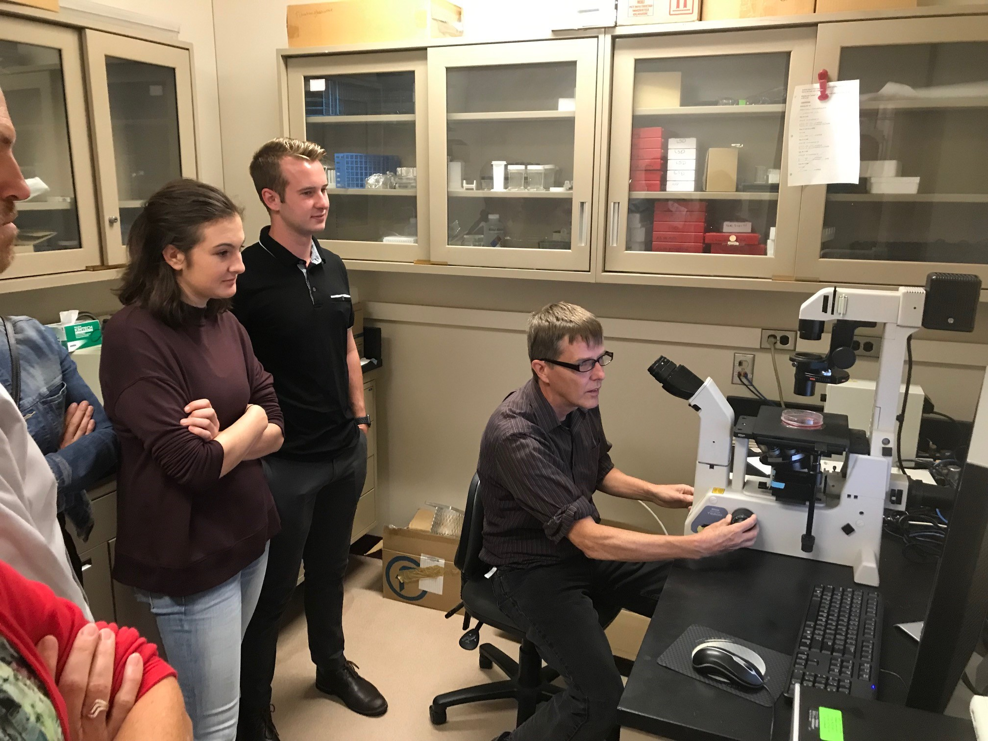 Dr. Tim Starr demonstrated how cancer cells are identified through a high powered microscope in his lab.