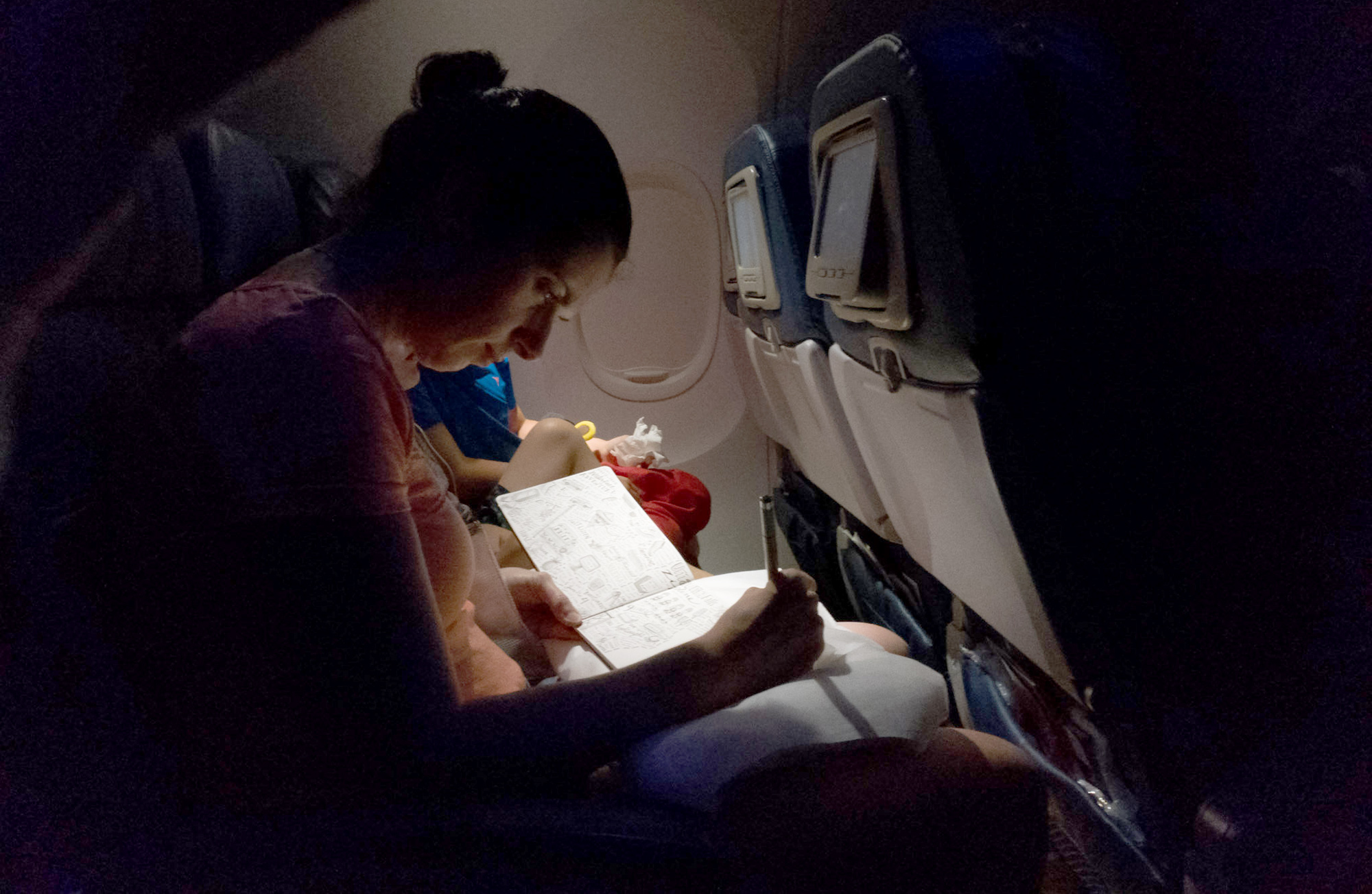 Finishing a drawing on an overnight flight. Thanks to the husband and family paparazzo, Matthew, for capturing it! xo