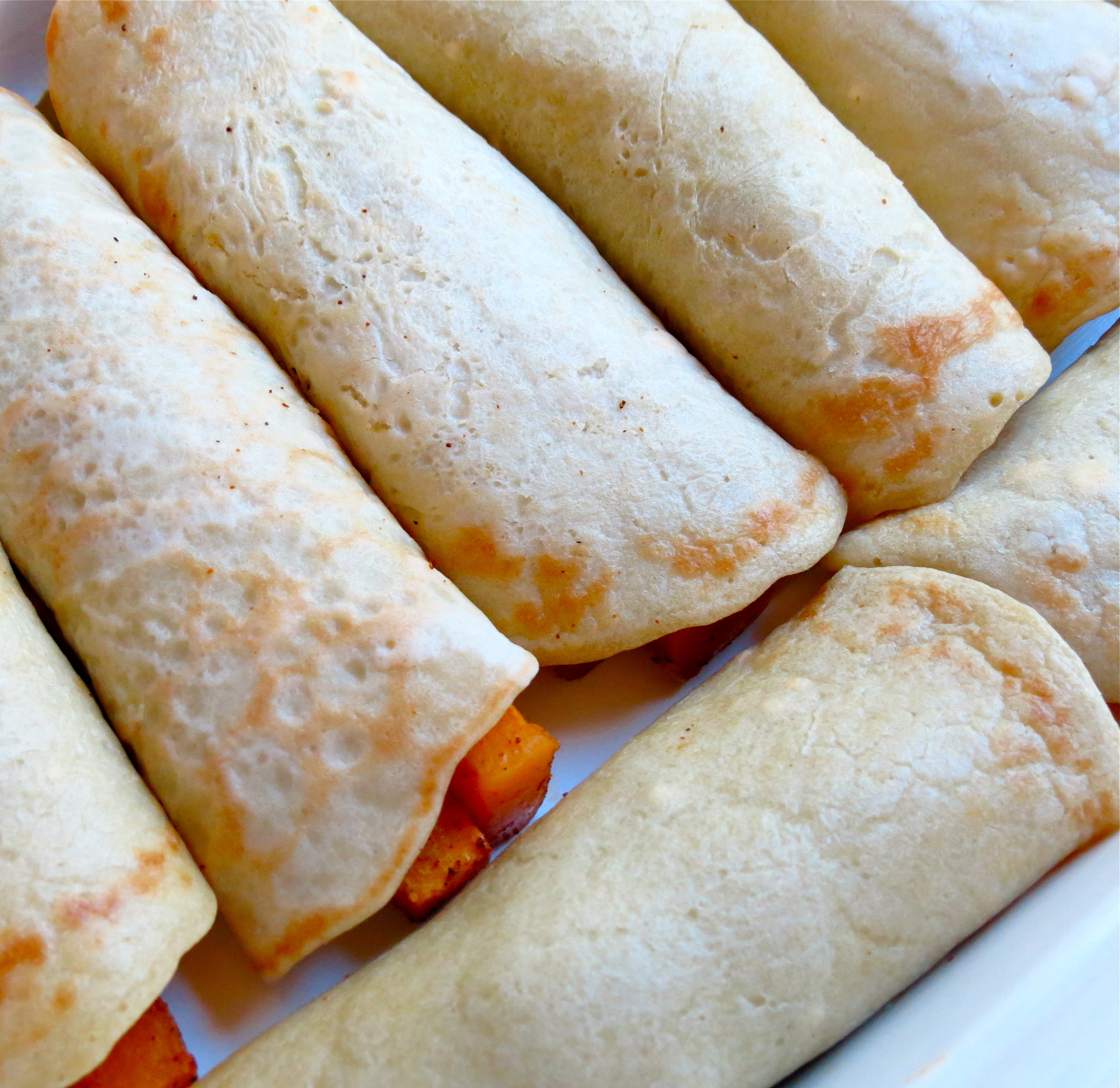 Enchiladas rolled up and placed in a baking dish.