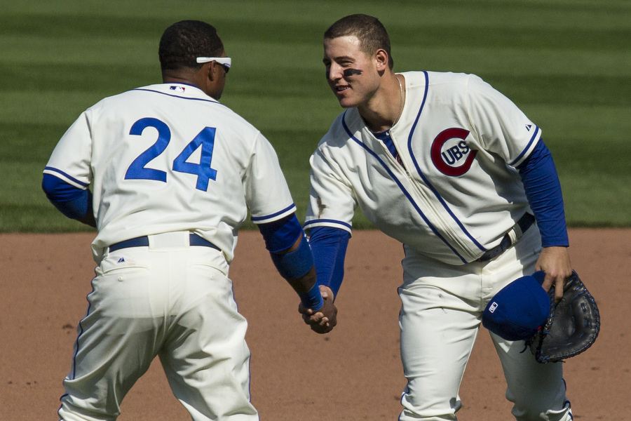 Infielders Luis Valbuena and Anthony Rizzo shake hands after defeating the Brewers.