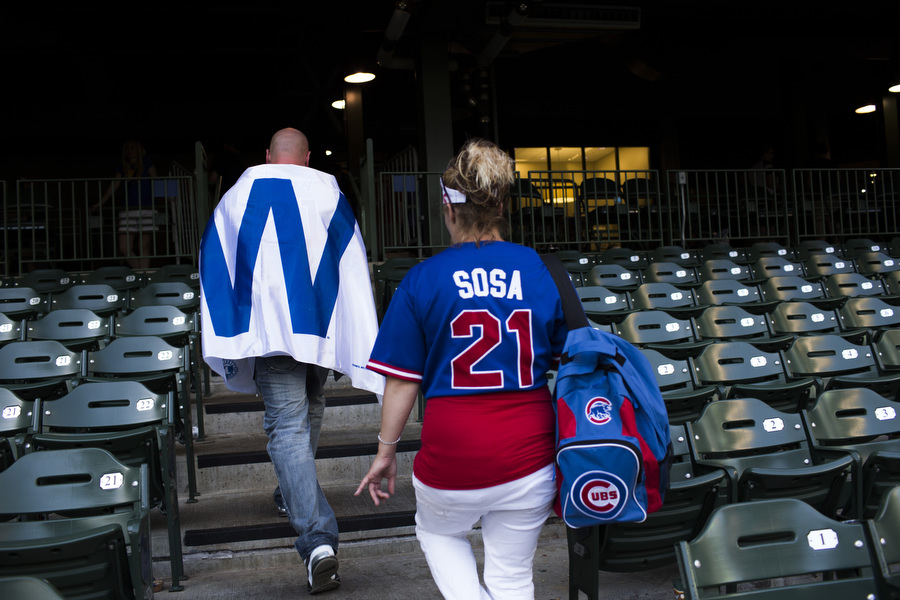 "Jim Krug and Sheila Krug leave Miller Park. Krug draped himself in a replica of the W flag that flies over Wrigley Field when the Cubs win. A Brewers usher came up to him and said, ""Now I don't like to get partisan but if all you've got in 100 years is a flag, there's something wrong with that."""