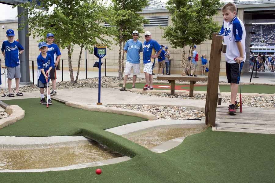 Brenden, second to right, hits a golf ball in a mini-golf game asTeegan,Caden,Mark, Daryl andDustin look on.