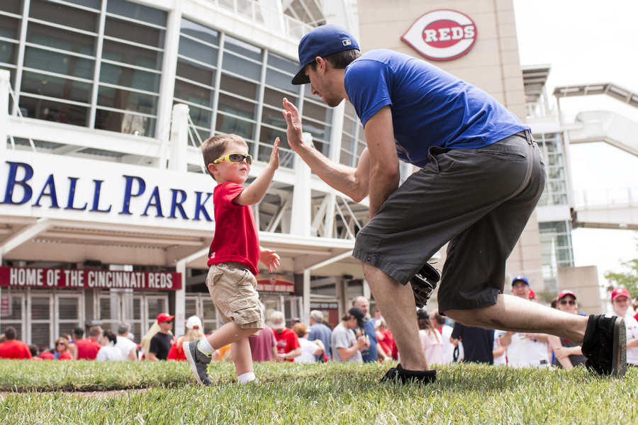 Before the gates open at Great American Ballpark, Jackson, 3, high fives Alex after they played a game of imaginary catch.