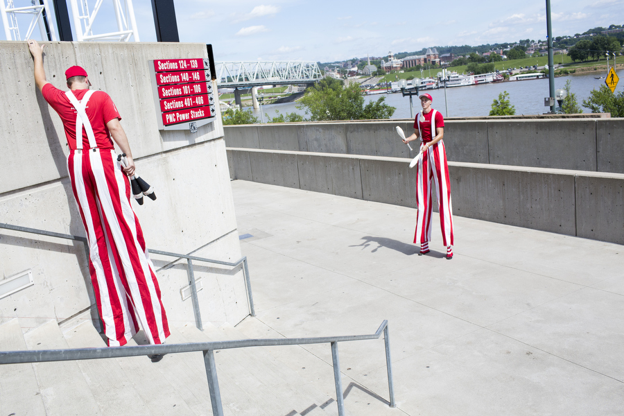 From right, stilted jugglers Adam and Brian of the Cincinnati Circus Company walk from one outfield section to another.