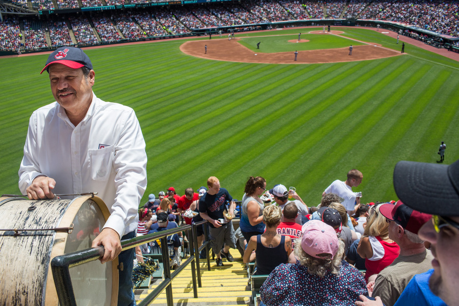 John Adams walks up the bleacher stairs with his bass drum to take his customary position in the top row. He's played that drum at more than 3000 games since 1973.
