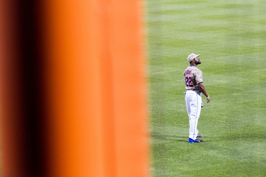 The Mets are the only team in baseball to have foul poles that aren't yellow. Here, Eric Young Jr. looks out before the start of an inning.