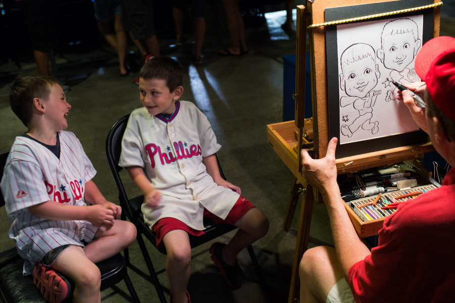 Cash, left, and Jaden get a caricature drawing at the game.